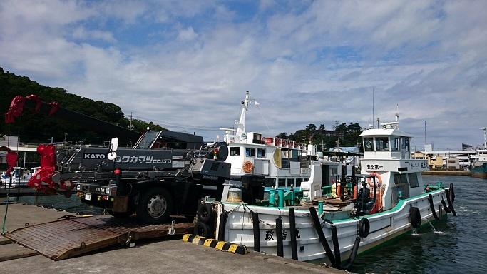 工事用足場の材料を積んだトラックが、船で港に到着