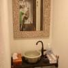 洗面所の鏡はココナッツのミラーを設置し、手を洗う所にも変わった形のつる首水洗を設置しました。