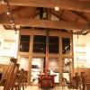 大きく吹き抜けた登り梁に杉板の羽目板、ファンで空気を移動させる大きな屋根。暖炉の煙突が見た目の温かさを感じさせます。